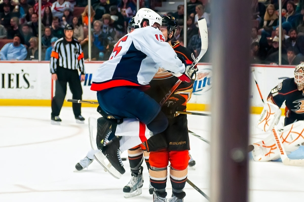 ANAHEIM, CA - February 16, 2011:  Washington Capitals forward Boyd Gordon (#15) jumps to avoid being hit by a puck on a shot from point after winning a third period faceoff against Anaheim Ducks forward Brandon McMillan (#64) during their NHL ice hockey game at Honda Center.