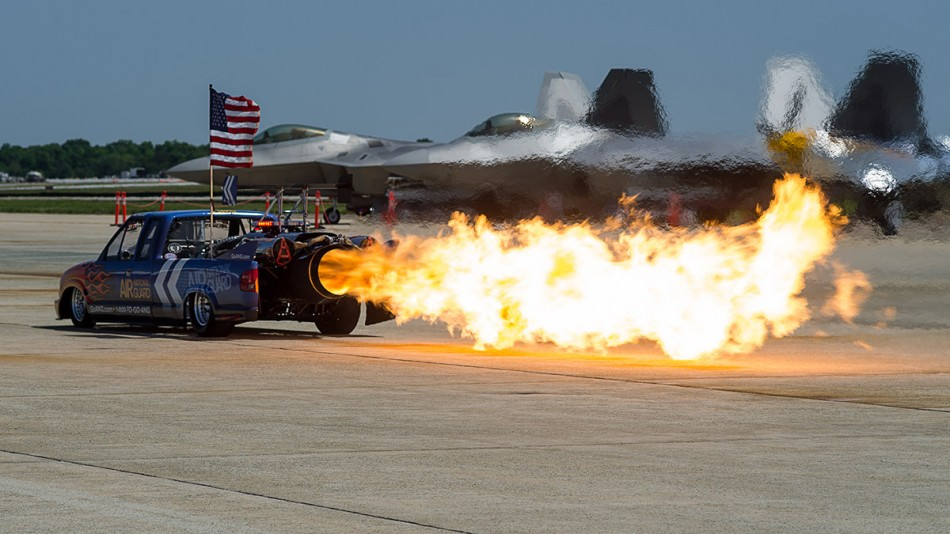 Joint Base Andrews, MD - May 19, 2012: Neal Darnell leaves a trail of flames behind his Air National Guard sponsored jet trucking front of two F-22 Raptor fighter planes and the P-51 Mustang &quot;Bald Eagle&quot; on the tarmac of Joint Base Andrews as part of the 2012 Joint Services Open House.