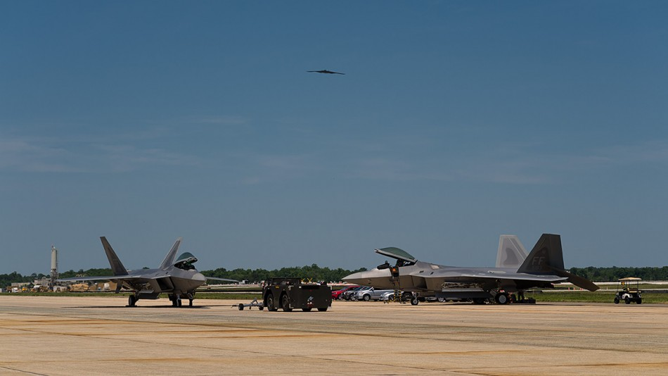 "Joint Base Andrews, MD - May 19, 2012: The B-2 Spirit bomber ""Spirit of Nebraska"" flies above Joint Base Andrews as part of the 2012 Joint Services Open House while an F-22 Raptor returns from an aerial demonstration routine."