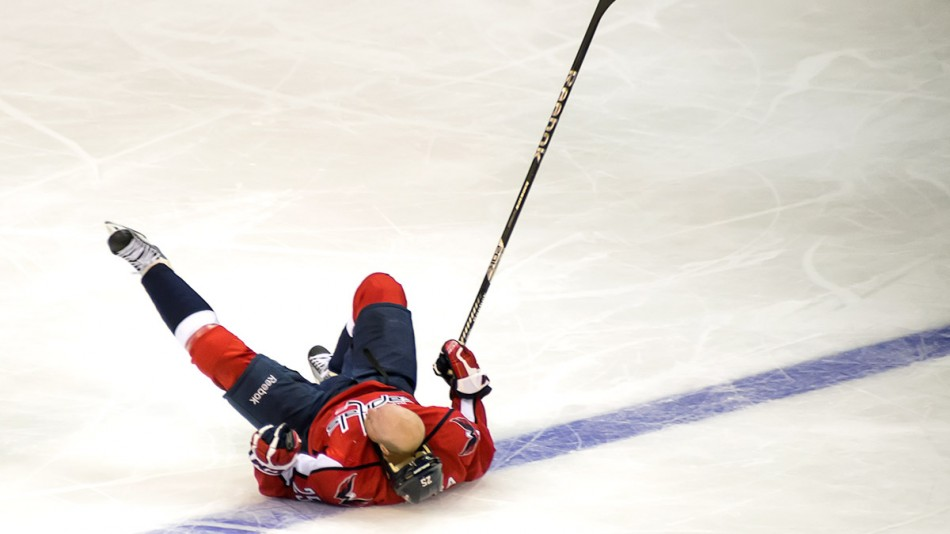 WASHINGTON, DC - January 22, 2013:  Washington Capitals forward Jason Chimera (#25) falls to the ice after colliding with Winnipeg Jets defenseman Grant Clitsome (#24) during their NHL ice hockey game at Verizon Center.
